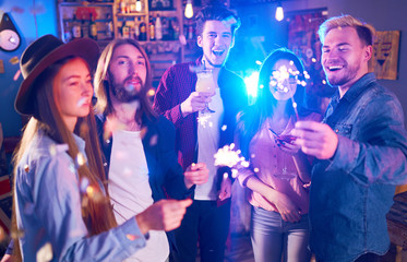 Young Group of Friends Partying In A Nightclub And Toasting Drinks. Happy Young People With Sparklers At Pub. The People Have A Great Mood And They Smile A Lot.