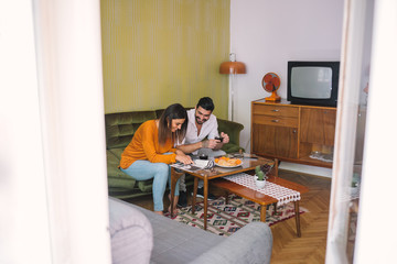 Friends Reading Magazine over Breakfast in Living Room