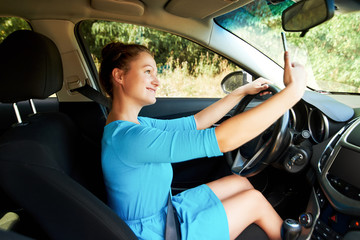 Happy young woman holding mobile phone and taking photos while driving a car. Smiling girl taking selfie picture with cellphone camera outdoors in car. Holidays and tourism concept