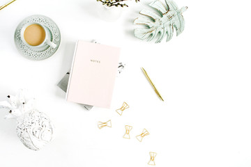 Home office desk. Workspace with pale pastel pink notebook, coffee and decorations on white background. Flat lay, top view.