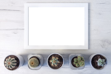 Top view of a wooden desk, white blank frame and several cactuses