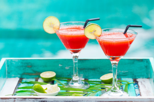 Strawberry margarita cocktail on colorful wooden background with palm leaf. Copy space