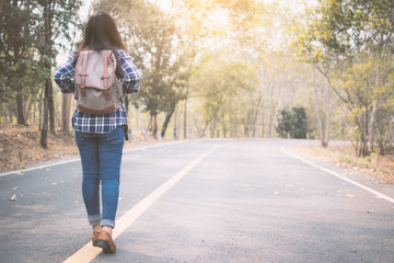 Happy Asian woman backpack in the road and forest background, Relax time on holiday concept travel ,color of vintage tone and soft focus