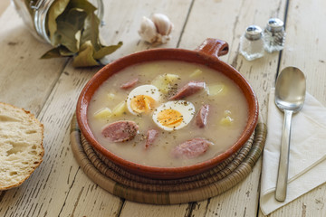 Traditional polish soup called Zurek served with bread