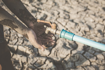 Hand of boy want to drink some water on crack ground , Concept drought and shortage of water crisis