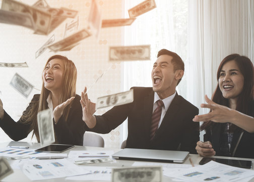 Business team parter celebrating profit by throwing money