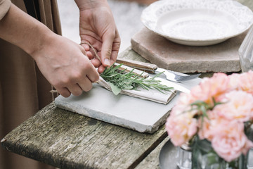 Woman decorating napkin with fresh green