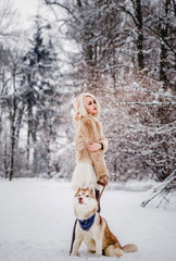 A sophisticated woman in a fur coat stands with her dog