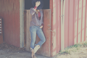 Cowgirl on agriculture ranch in red barn on sunny day.  Woman standing against the wall in western wear.