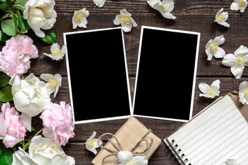blank photo frame with roses and jasmine flowers, gift box and lined notebook