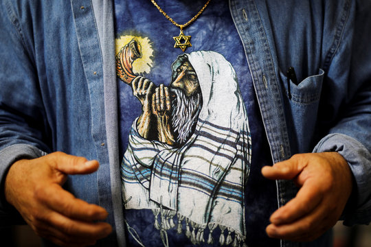 A print of an orthodox Jewish man sounding the Shofar, a ram's horn, is seen on the shirt of Shofar maker Robert Weinger, in his workshop in Rishon Lezion