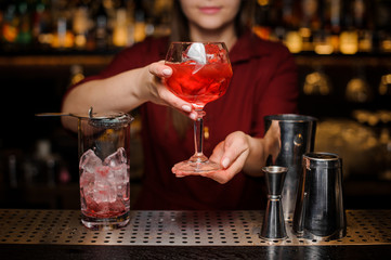 Bartender girl serving a light red cocktail