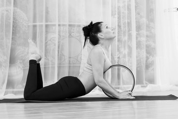 A middle-aged woman does yoga with a wheel.