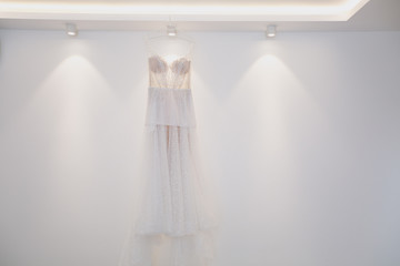 A beautiful tender elegant wedding dress with lace and thin straps for the bride hangs on a hanger against the background of a white wall and light bulbs. Wedding wear, accessories