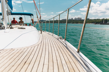 Sailing boat deck on a white yacht with teak wooden deck, metal railing, set of red ropes with people on board in the sea near the coastline in the background blue sky with clouds in sunny day