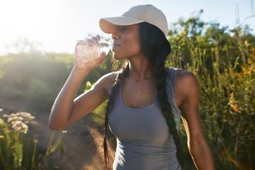 fit female hiker taking a break to drink water from waterbottle