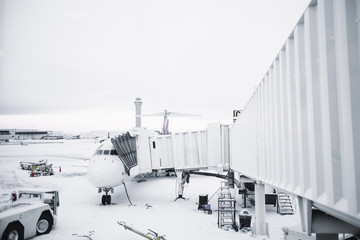 Airplane waiting at terminal with a snow covered ground