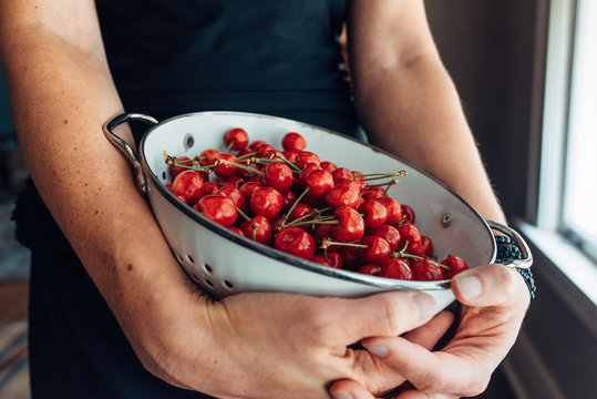 Woman's hands holding a bowl of cherries