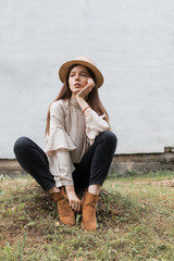 Beautiful young girl in a hat sits