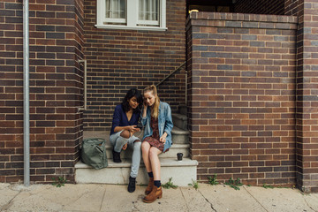 Two Young Women Listen to Music on Stairs