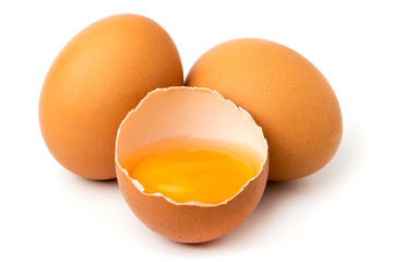 Chicken eggs and half with yolk on a white background.