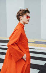 Young woman with orange trench coat and eyeglasses
