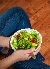 Green vegan breakfast meal in bowl with various fresh mix salad leaves and tomato. Girl in jeans holding fork with knees and hands visible, top view on wooden background