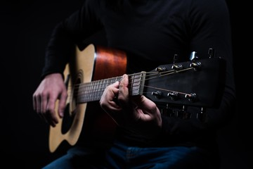 A man is playing an acoustic guitar while sitting