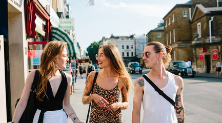 Three friends chatting and walking in London