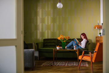 Young Woman Reading a Book in the Living Room