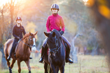 Group of rider girls riding their horses in park. Equestrian recreation activities background with copy space Wall mural