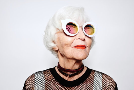 Smiling senior woman in stylish sunglasses and shirt