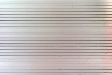 Background from horizontal straight lines. Pale pink wall of unusual stripes, laths.
