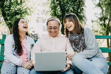 .A father with his daughters sitting on a stone bench, learning to use the laptop. Relaxed autumn day in family outdoors. Lifestyle portrait...