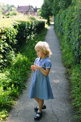 Little girl in summer school uniform stands on a path in England.