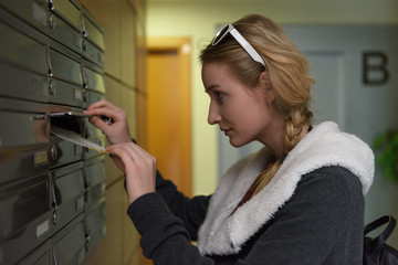 Young woman taking letter from box