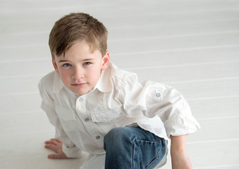 Boy sitting on white floor