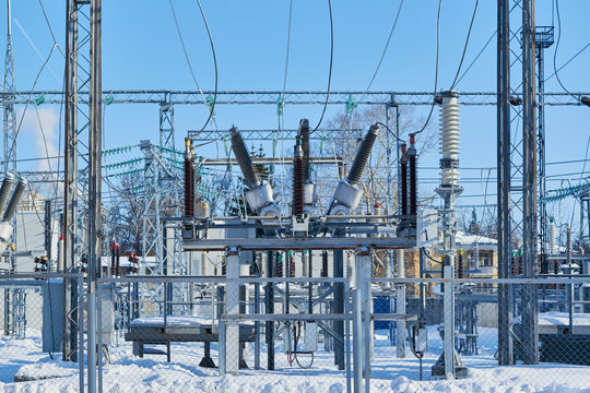 High-voltage circuit breakers at electrical substations connected with electric wires. Insulators on circuit breakers. The supply and distribution of electricity. The territory is fenced. Winter.
