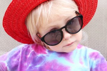 Cute little Girl in Summer Hat and Sunglasses Making Serious Face at Camera