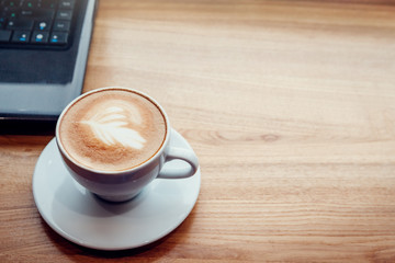 Drinking coffee while using a laptop in cafe. Cup of coffee with laptop in font of the window