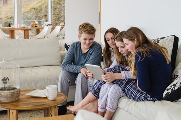 group of teenagers in pjs, on sofa with ipad