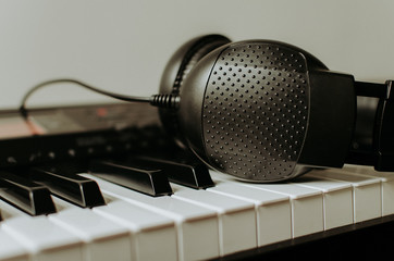 Piano keyboard keys and headphones close up