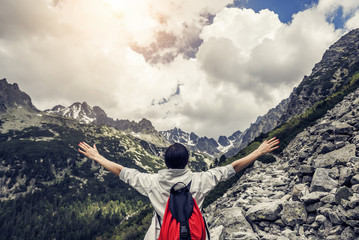 Tourist with hands up stands on the background of a mountain landscape.
