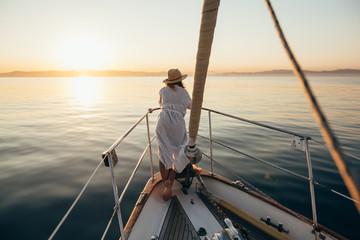 Beautiful woman enjoying the sunset on sailboat.