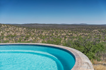 Pool with chairs overlooking the Namibian African savannah.