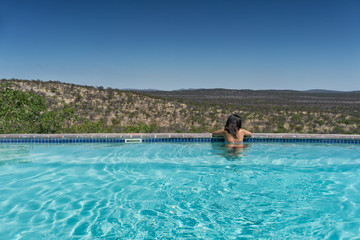 Young girl in the pool overlooking the Nambian savannah. Africa.