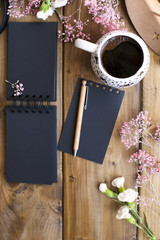 Aramatic coffee in a mug. Planning the day in a black notepad. Decor of pink flowers on a wooden table. Free space for text. Card.