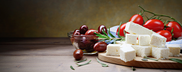Feta cheese with kalamata olives, tomatoes and rosemary on a wooden background with space for text