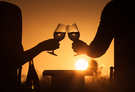 Couple celebrating outdoors with a glass of wine and beautiful sunset.  Happy life moments, romance, concept.