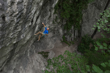 Side view of male rock climber hanging on craggy rock wall